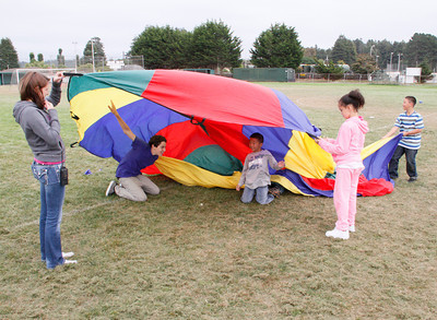 Shaun Walker/The Times-Standard  Youth play with a parachute during the Washington After School program in Eureka on Friday afternoon. Participants also played games with balls and other activities.