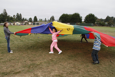 Shaun Walker/The Times-Standard  Jayda Alcutt, 8, center, and others play with a parachute during the Washington After School program in Eureka on Friday afternoon. Participants also played games with balls and other activities.
