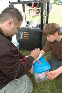 Austin Owsley, 10, gets a temporary airbrushed tatoo from Jorge Janeiro of Bodyart Express at Pierson Park in McKinleyville during the Azalea Festival on Saturday.