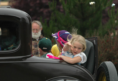 A young girl throws candy during the Pony Express Parade on Saturday in McKinleyville during the Azalea Festival.
