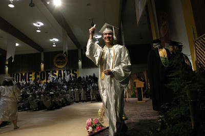 Josh Jackson/The Times-Standard  Damien Adams holds his diploma triumphantly during the College of the Redwoods commencement on Saturday.