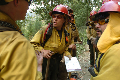 Mark McKenna/The Times-Standard Squad leader Molly Day, points to a map during a briefing with firefighters on a hillside near the Northern California town of Happy Camp. Several fires in the area have burned roughly 5,000 acres and the entire incident is being called the Elk Complex Fire.