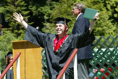 Shaun Walker/The Times-Standard  Nicholas Miller celebrates after getting his diploma holder. Actual diplomas were handed out in the cafeteria afterward.