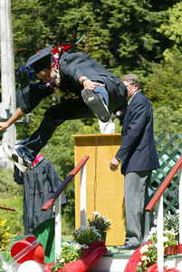 Shaun Walker/The Times-Standard  Gregory Keller jumps down after getting his diploma holder.