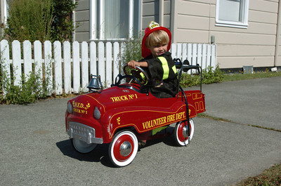 Mark McKenna/The Times-Standard Jessiah Class rides his toy firetruck outside his family's home in Arcata.