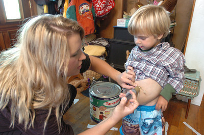 """Mark McKenna/ The Times-Standard Helena Class helps her brother Jessiah with a """"food push."""" Jessiah receives food through a Mic-Key button, a device that connects directly to his stomach."""