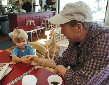 Mark McKenna/The Times-Standard Jessiah Class thumb wrestles uncle Greg Schupp at Brio in Arcata.