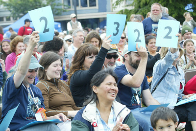 Shaun Walker/The Times-Standard  Judges show scores and smiles during the oystert calling contest.