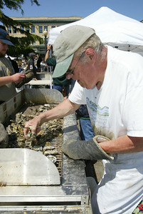 Shaun Walker/The Times-Standard  Robert Meyer of Mad River Farms shucks and grills oysters.