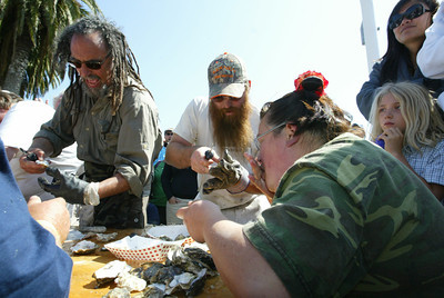 Shaun Walker/The Times-Standard  Volunteer oyster eater Malia Penhall slurps down oysters shucked by Aqua-Rodeo Farms' Steve Bohner, center, as Smokin' Moses shucks for his team in a very messy competition.