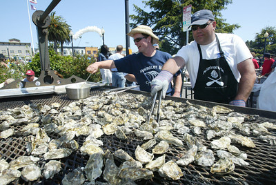 Shaun Walker/The Times-Standard  Humboldt Bay Oysters Owner Todd Van Herpe and friend Dean Flint tend to a large grill full of hot oysters.