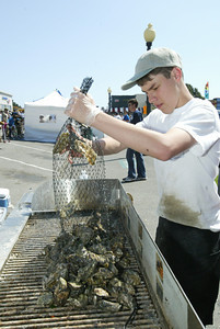 Shaun Walker/The Times-Standard  Matthew Myrick dumps another bag of local Pacific oysters on the Mad River Farms grill.