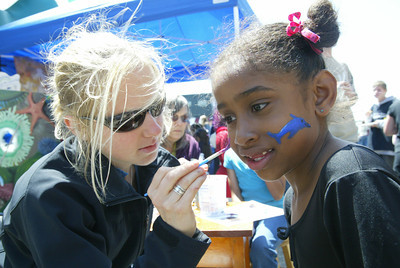 Shaun Walker/The Times-Standard  Chelsea Kuiper of Bayside paints the face of Alana Busby, 6, of Arcata at the HSU Natural History Museum tent in the kids area.