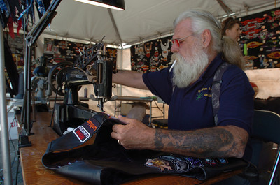 Mark McKenna/The Times-Standard  A man calling himself Lord P.M. Christ, sews a patch on to a leather vest at a gas station near the Redwood Run.
