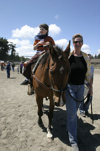 Josh Jackson/The Times-Standard  Jonathan Daw gets a horseback ride with Cass Doss leading during the Exceptional Olympics during the Redwood Acres Fair and Rodeo on Saturday. About 200 kids took turns roping and riding under the guidance of experienced horsemen and women.