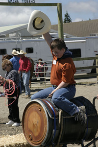 Josh Jackson/The Times-Standard  Justin Hamblin gets his full eight seconds during the Exceptional Olympics during the Redwood Acres Fair and Rodeo on Saturday. About 200 kids took turns roping and riding under the guidance of experienced horsemen and women.