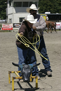 Josh Jackson/The Times-Standard  Joe Rosa helps Keith White learn steer roping during the Exceptional Olympics during the Redwood Acres Fair and Rodeo on Saturday. About 200 kids took turns roping and riding under the guidance of experienced horsemen and women.