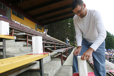 """Josh Jackson/The Times-Standard  Kurt Medeiros helps set up the luminaria in the granstands that spell out the word """"HOPE""""  during the 2007 Relay for Life at College of the Redwoods on Friday."""