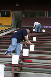 """Josh Jackson/The Times-Standard  Ben Davenport helps set up the luminaria in the grandstands that spell out the word """"HOPE""""  during the 2007 Relay for Life at College of the Redwoods on Friday."""