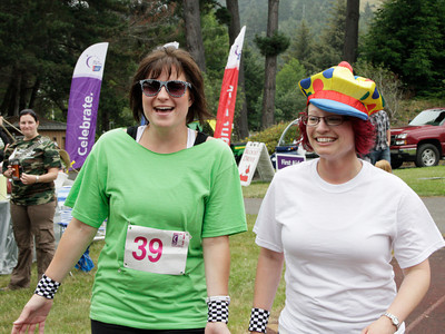 Shaun Walker/The Times-Standard  Anna Taylor, left, and Jenna Tronti of Drivin' for a Cure team  laugh and walk at Humboldt Relay for Life 2012 on Saturday.