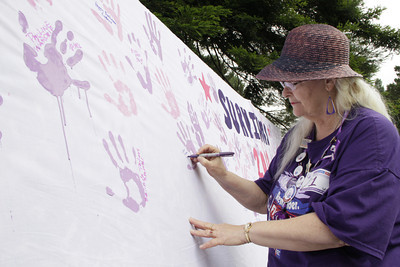 Shaun Walker/The Times-Standard  Kidney cancer survivor Janet Koppri of Eureka signs her name next to her hand print at Humboldt Relay for Life 2012 on Saturday.
