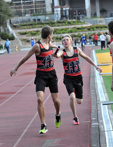 JosŽ Quezada/For the Times-Standard  Michael Davis,right, stretches out to hand the baton to teammate Jason Coley in the first pass for the winning McKinleyville High School 4 x 800m relay.