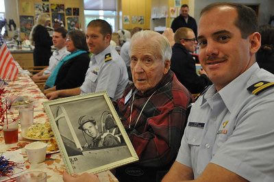 José Quezada/For the Times-Standard  World War II Army Air Force test pilot Joe Moyer sits with Coast Guard helicopter pilot Roger Barr holding a picture of himself in one of his test airplanes during the war.   Adult Day Health Care of Mad River joined forces with the Coast Guard from the Samoa boat station and the McKinleyville air station to honor local veterans on Tuesday.