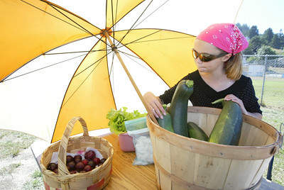 Shaun Walker/The Times-Standard  Belle Snow, 11, tends to produce from Al and Carolin Petrovich's Rio Dell farm at the Rio Dell Farmers Market on Wednesday. The market is open on Wednesdays from 3 to 6 p.m. next to the Chamber of Commerce on Wildwood Avenue.