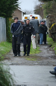 Mark McKenna/The Times-Standard Eureka Police Officer Gary Whitmer leads an unidentified youth out of an abandoned house at 3200 Albee Street in Eureka shortly after officers shot and killed Zachary Cruz Cooke in January.