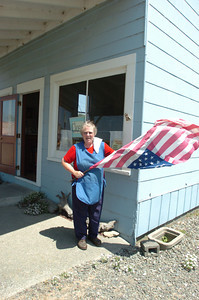 Mark McKenna/The Times-Standard Ingrid Pfeiffer takes down the flag outside Vern's Blue Room in Ferndale. She is closing down after 31 years in business.