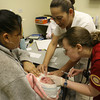 Pittsburg State University nursing student Amber Foraker, right, and nurse Luz Elena Hernandez crowd around Reyna Rosas Rosas (cq) and her as yet un-named 8-day-old daughter as Foraker administers a tuberculosis vaccination at Juarez's Hospital de la Familia.  Twenty nursing students from Pittsburg, Kansas spent one week at the hospital for some hands-on training.  Photo by Adriane Jaeckle / El Paso Times