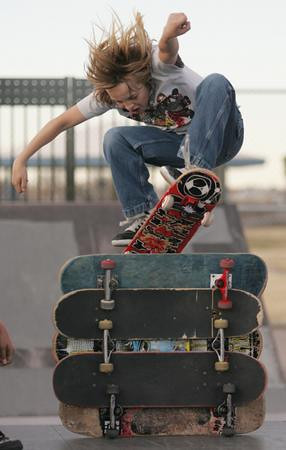 Joey Ashry, 12, attempts an ollie over five stacked skateboards while riding at Veterans Park. Adriane Jaeckle / El Paso Times.