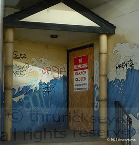 This entrance to a closed garage has been customized over time by graffiti artists.