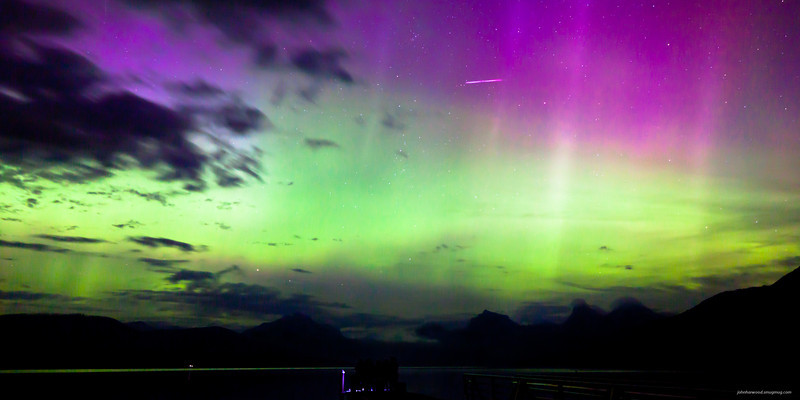 Family watching the northern lights & shooting star over Lake Mc Donald in Glacier National Park