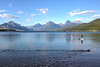 Couple and dog paddleboarding on Lake McDonald in Glacier National Park