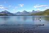 Couple and dog paddleboarding on Lake McDonald in Glacier National Park