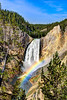 Rainbow at the base of Canyon Falls in Yellowstone with blue sky