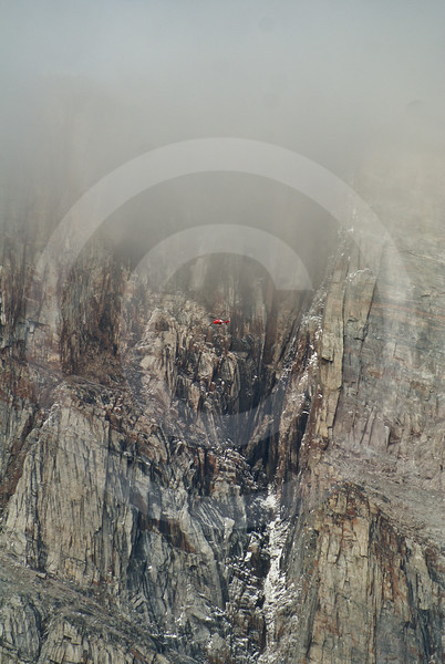 (278) The Amundsen's helicopter seems microscopic when flying along the towering cliffs of Gibbs Fjord, Baffin Island, Nunavut