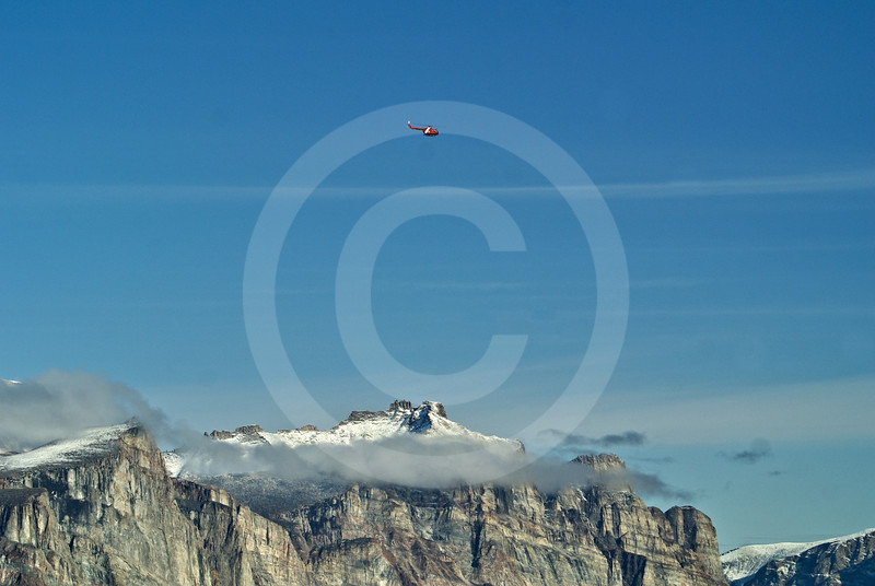 (276) The Amundsen's helicopter seems microscopic when flying along the towering cliffs of Gibbs Fjord, Baffin Island, Nunavut