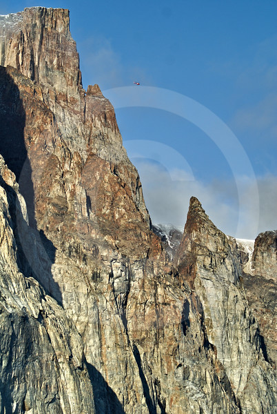 (275) The Amundsen's helicopter seems microscopic when flying along the towering cliffs of Gibbs Fjord, Baffin Island, Nunavut