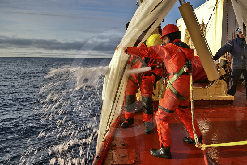 (225) ArcticNet scientists and Coast Guard personnel rinsing plankton nets on the foredeck of the CCGS Amundsen