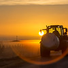(2319) farmer driving with a round bale of silage  in the afternoon sun.