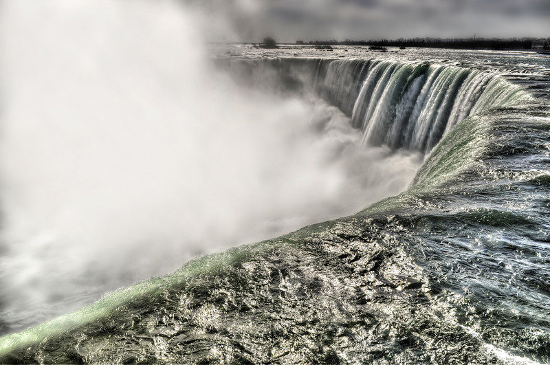 "The Niagara Falls, located on the Niagara River draining Lake Erie into Lake Ontario, is the collective name for the Horseshoe Falls and the adjacent American Falls along with the comparatively small Bridal Veil Falls. The features that became Niagara Falls were created by the Wisconsin glaciation about 10,000 years ago. The same forces also created the North American Great Lakes and the Niagara River.<br /> In October 1829, Sam Patch, who called himself ""the Yankee Leapster"", jumped from a high tower into the gorge below the falls and survived; this began a long tradition of daredevils trying to go over the falls. <br /> The number of visitors in 2007 was expected to total 20 million and by 2009, the annual rate was up to top 28 million tourists a year."