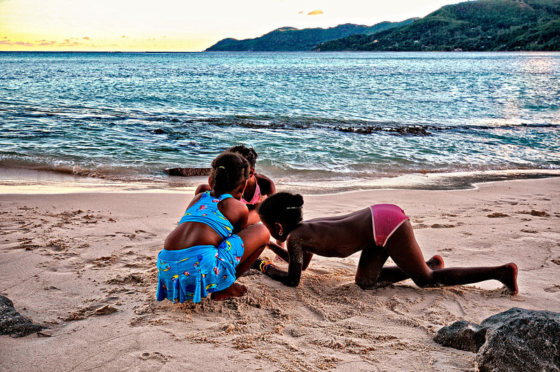 Kids play with the sand. Somewhere in Mahe.