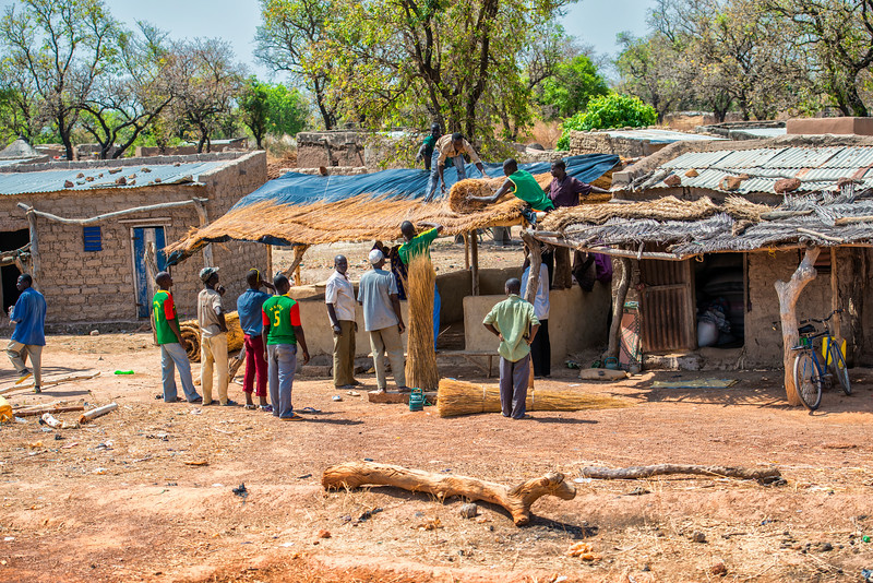 Sun, Heat, Village. People helping each other to build house. Mali.