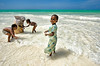 Kids don't care about religion, playing together with the Ocean waves. Muslims and Masai.<br /> Zanzibar