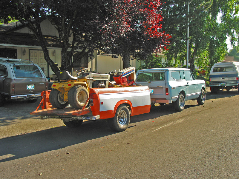 1976 Scout II hooked to a trailer made from a 1975 IH pickup, hauling an IH Cub Cadet 129 and a Spirit of 76 Cadet.  1978 Scout Traveler in the driveway.