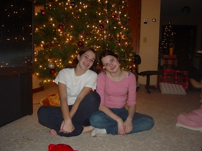 Nicky and Liz, sweet and innocent, sit in front of the tree.