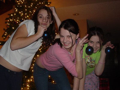 The girls being silly decorating the tree.