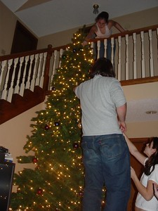 Zack is the only one tall enough to decorate the middle of the tree.